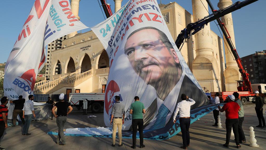 Los trabajadores ajustan un cartel del presidente Recep Tayyip Erdogan en Mardin, capital de la provincia de Mardin en el sureste de Turquía, el 19 de junio de 2018.