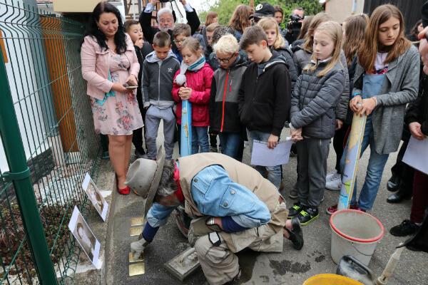 Les élèves de l'école de Muttersholtz rassemblés autour de Gunter Demnig lors de la pose de pavés