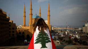 A Lebanese anti-government protester draped in a national flag sits on a rooftop overlooking Mohammed al-Amin mosque and Martyrs Square in downtown Beirut