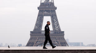 A police officer patrols the Trocadero square, facing the Eiffel Tower in Paris, on day one of France's coronavirus lockdown.