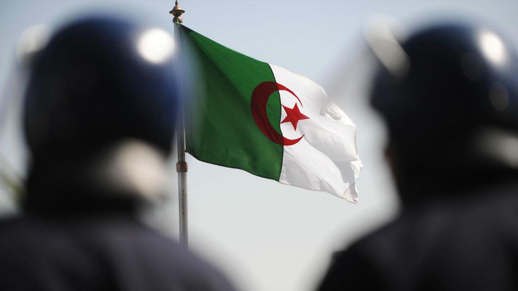 Deux policiers à Alger, en 2011, avec le drapeau algérien en fond. (photo d'illustration)