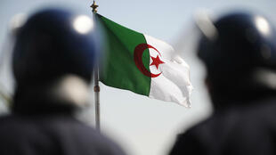 Two Algerian policemen stand together against a backdrop of the national flag in Algiers on March 7, 2011.