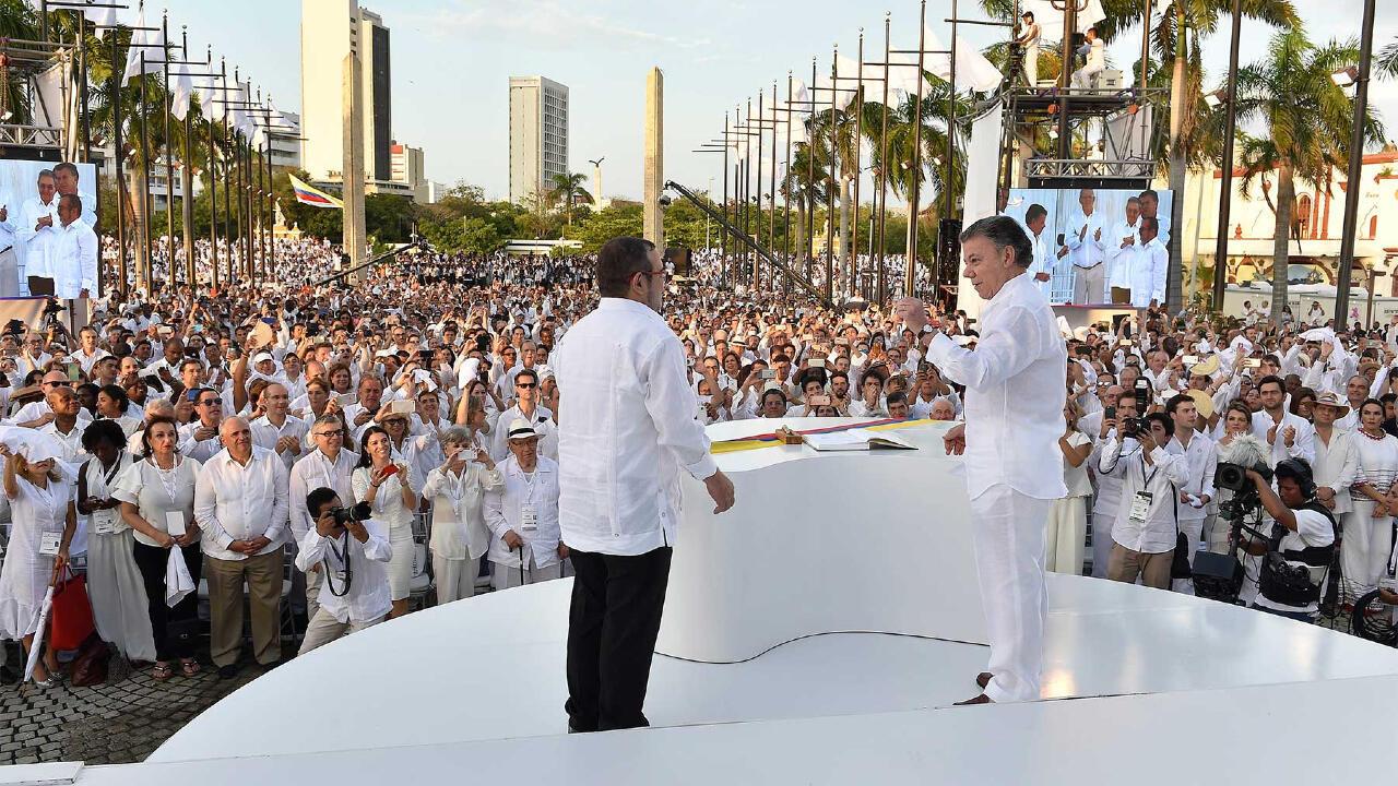 El entonces presidente Juan Manuel Santos (d) y Rodrigo Londoño, alias 'Timochenko' y jefe de las FARC, firmaron el primer acuerdo de paz en Cartagena, Colombia, el 26 de septiembre de 2016. Foto de archivo.