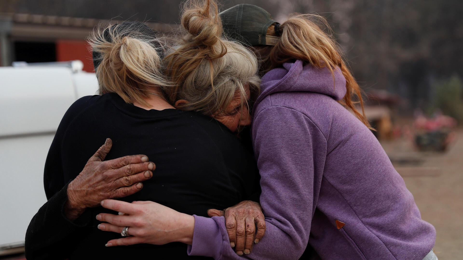 Cathy Fallon (C), quien se quedó para atender a sus caballos durante el paso del Camp Fire , abraza a Shawna De Long (I) y April Smith, quienes trajeron suministros para sus caballos en Paradise, California. El dr