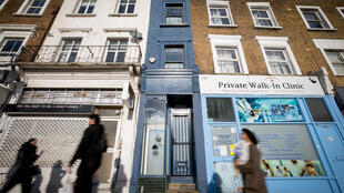 Des passants devant la façade bleue de la plus étroite maison de Londres (Royaume-Uni), le 5 février 2021