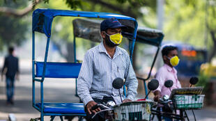 سائقا عربتين يرتديان قناعين واقيين وينتظران ركاباً في نيودلهي في الهند في 19 أيار/مايو 2020