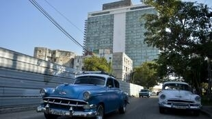 Old American cars drive near the emblematic Hotel Habana Libre, which could be affected if the United States activated Title III of the Helms-Burton Act