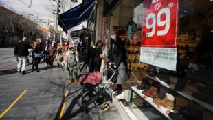Une cliente quitte un magasin de chaussures, à Jérusalem, le 21 février 2021, alors qu'Israël rouvre des pans entiers de son économie.