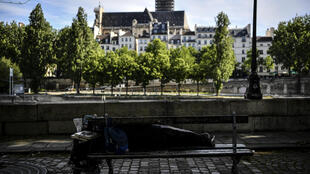 A homeless man sleeps on a bench on Paris's Île Saint-Louis on May 18, 2020.