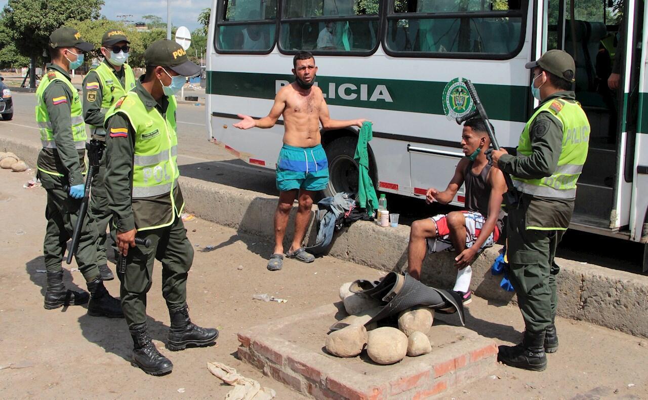 Policías de Colombia hablan con ciudadanos venezolanos que incumplen con las medidas de restricción de movilidad por alerta roja sanitaria, debido al contagio por coronavirus, este viernes en Cúcuta (Colombia).