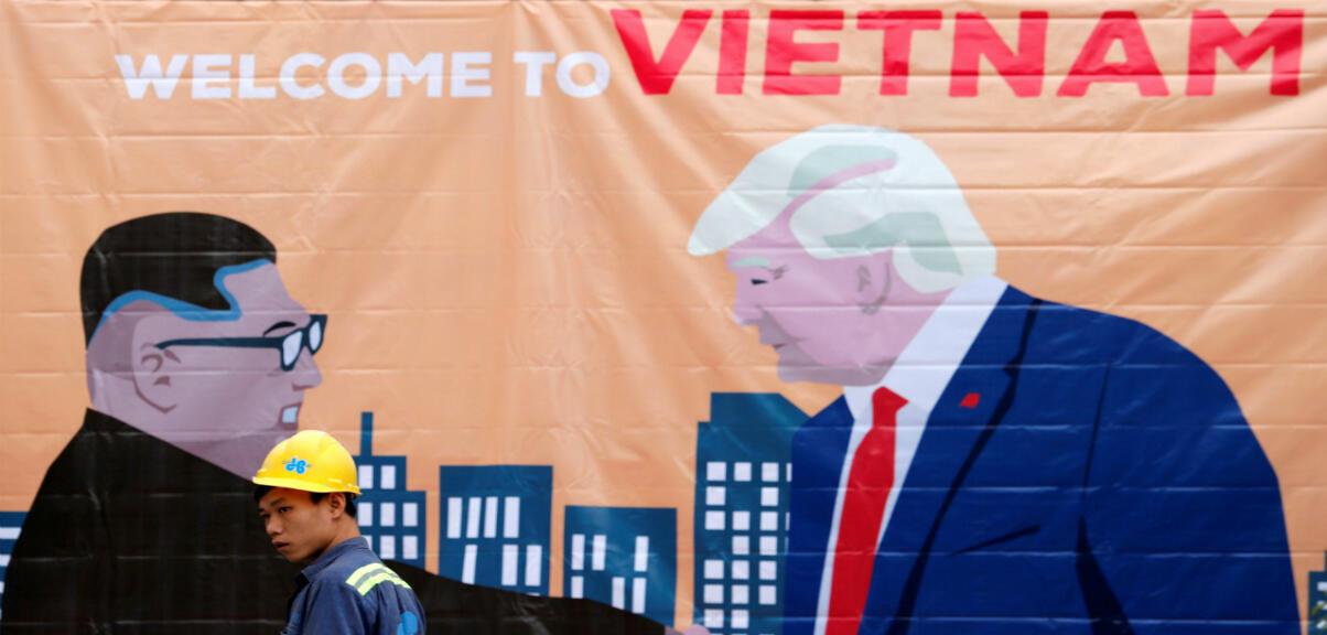 Un hombre pasa frente a una pancarta que representa al líder norcoreano Kim Jong Un y al presidente de Estados Unidos Donald Trump antes de la cumbre entre Corea del Norte y Estados Unidos en Hanoi, Vietnam, el 25 de febrero de 2019.