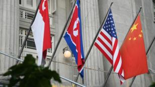 Les drapeaux singapourien, nord-coréen, américain et chinois sur la façade de l'hôtel Fullerton, cadre du sommet Trump-Kim.
