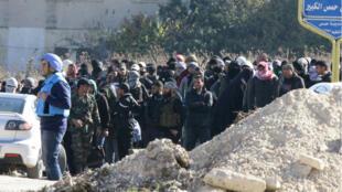 Les forces syriennes ont monté la garde pour permettre l'évacuation des rebelles et civils du quartier de Waer à Homs en Syrie, le 9 décembre 2015.