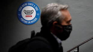 """A man wearing a protective face mask walks past a sign reading """"Mandatory mask. For our common health, wear a mask """" at a Paris metro station on May 5, 2020."""