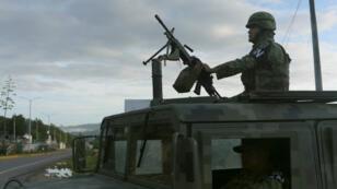 Un miembro de la Guardia Nacional vigila un vehículo militar en un punto de control en Comitán, estado de Chiapas, México, el 16 de junio de 2019.