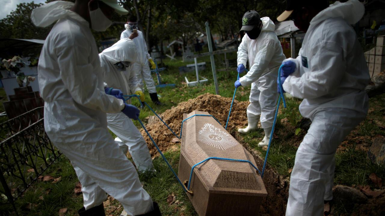 Sepultureros con trajes protectores entierran el ataúd de Manuel Farias, de 70 años, quien murió a causa del coronavirus en el cementerio Recanto da Paz, en Breves, al suroeste de la isla de Marajo en el estado de Pará, Brasil, el 7 de junio. 2020.