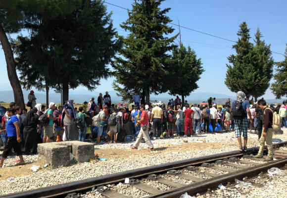 Migrants wait patiently in the baking heat at the tiny railway station of Idomeni, on Greece's border with Macedonia. (Photo: Fernande van Tets)