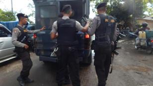 Indonesian police escort an armored vehicle carrying Filipina drug convict Mary Jane Veloso to Nusakambangan maximum security prison island on April 24, 2015.