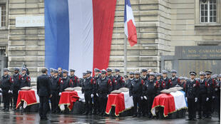 French President Emmanuel Macron stands in front of coffins during a ceremony at The Prefecture de Police de Paris (Paris Police Headquarters) in Paris on October 8, 2019.