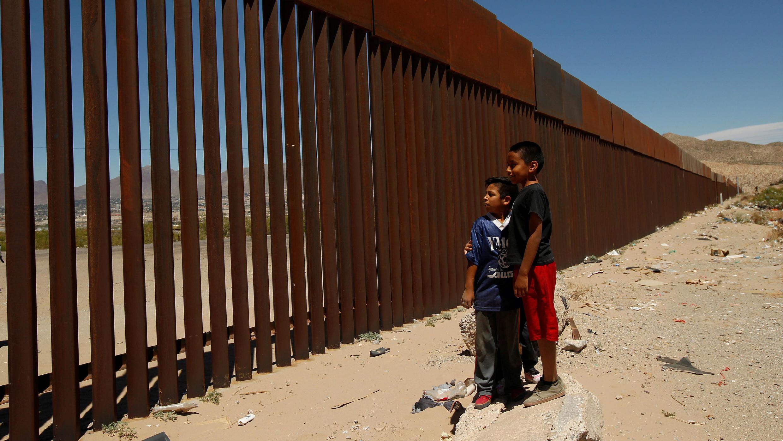 Dos niños miran parte de una cerca en Ciudad Juárez, en el lado mexicano de la frontera con Estados Unidos. 3 de mayo de 2018.