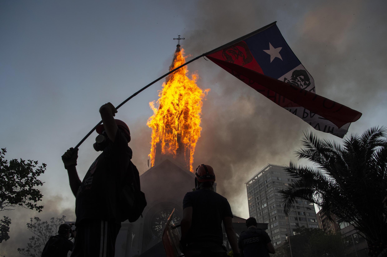 Un manifestante agita una bandera chilena frente a una iglesia en llamas durante las manifestaciones en Santiago, el 18 de octubre de 2020.