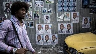 Un homme passe devant des affiches électorales à Lingwala, dans le nord de Kinshasa, le 18 décembre 2018.