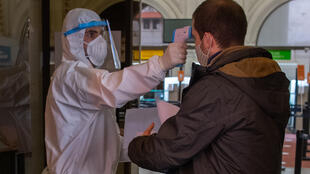 Un empleado con traje de protección verifica la temperatura de un pasajero que ingresa al terminal de la empresa de servicios de ferry Buquebus, que une Uruguay y Argentina, en el puerto uruguayo de Montevideo, el 10 de julio de 2020, en medio de la pandemia de coronavirus.