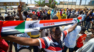 Un manifestante muestra un banner con los colores de la bandera de Sudán durante las protestas en Jartum, el 14 de mayo de 2019.