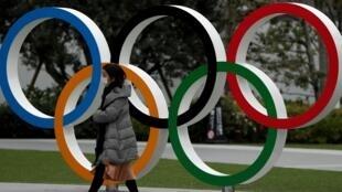 سيدة تسير مرتدية قناعا طبيا أمام شعار الألعاب الأولمبية قرب المتحف الأولمبي بطوكيو، 30 مارس/آذار 2020.