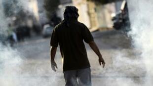 متظاهر بحريني يسير وسط دخان قنبلة غاز أطلقتها قوات الأمن خلال اشتباكات أعقبت تظاهرة ضد الحكومة في قرية سترة جنوب المنامة في 1 كانون الثاني/يناير 2016