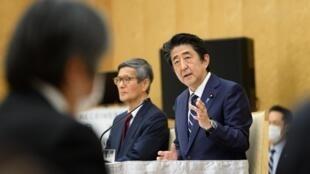 رئيس الوزراء الياباني شينزو آبي إلى جانب المستشار الصحي للحكومة شيغيرو أومي خلال مؤتمر صحافي في مكتب رئيس الوزراء، 14 أيار/مايو 2020