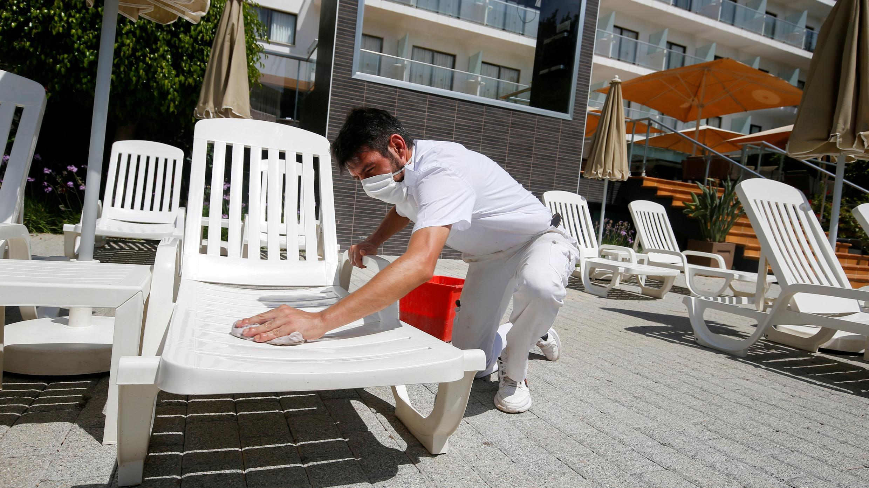 Un trabajador con una máscara facial protectora limpia una hamaca en el área de la piscina de un hotel en Playa de Palma, mientras España se prepara para reabrir oficialmente sus fronteras, en Palma de Mallorca, España, 14 de junio de 2020. Foto de archivo.