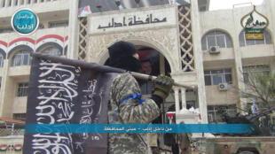 Un combattant jihadiste tient le drapeau du Front al-Nosra devant la préfecture d'Idleb.