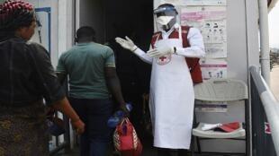 فني صحي يستقبل أشخاصا في مرفق فحص الصحة في مبوندوي على الحدود بين أوغندا و جمهورية الكونغو الديمقراطية، في 13 يونيو/حزيران 2019