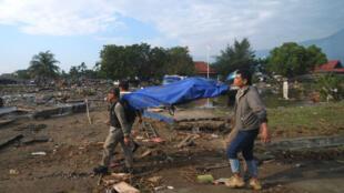 Des habitants de Palu transportent un corps à Palu, en Indonésie, l 29 septembre 2018.