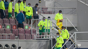 Shabab Al-Ahli players return to the changing rooms after match called off