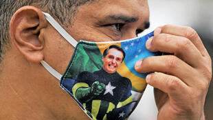 Brazilian president Jair Bolsonaro, whose image can be seen on this person's face mask, has further diluted a law mandating such masks in his country as it struggles with the coronavirus pandemic