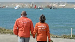 Les sauveteurs de la SNSM observent les marins qui naviguent sur leur bateau, le 10 juin 2019, aux Sables-d'Olonne, en hommage aux trois sauveteurs tués le 7 juin.