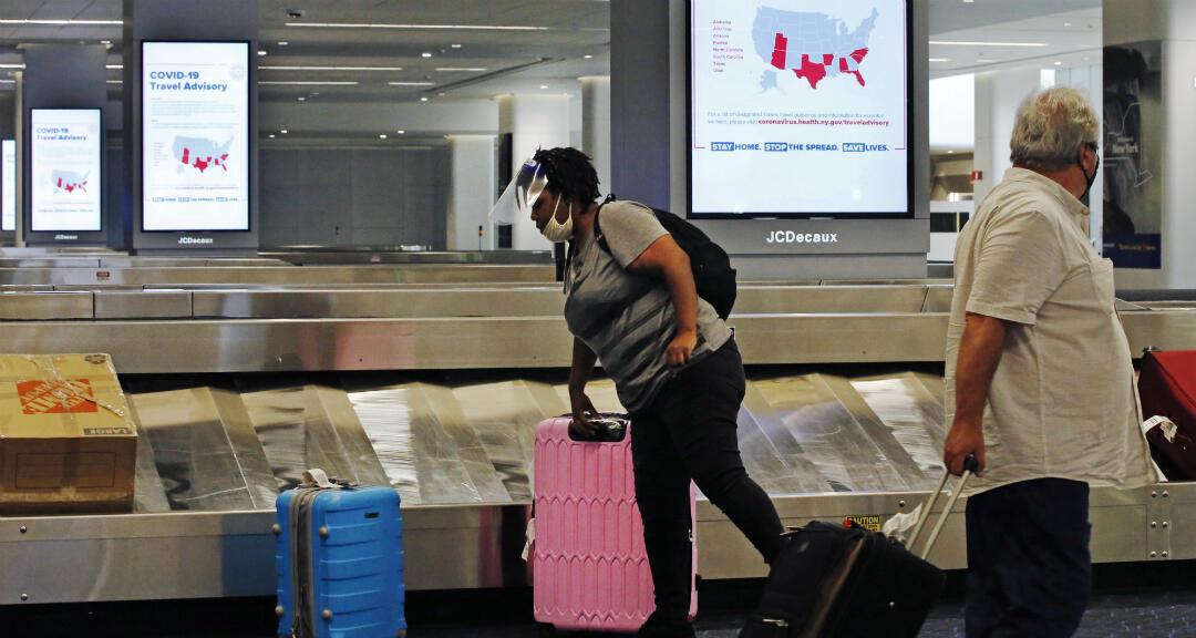 Un pasajero llega con un protector facial a recoger su equipaje en la Terminal B del Aeropuerto LaGuardia, el jueves 25 de junio de 2020, en Nueva York, EE. UU.