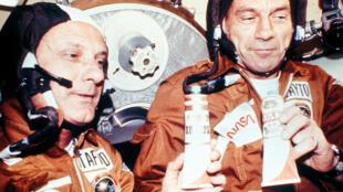 Deux astronautes américains trinquent avec des tubes portant des étiquettes de vodka, à bord d'un vaisseau Soyouz en 1975.