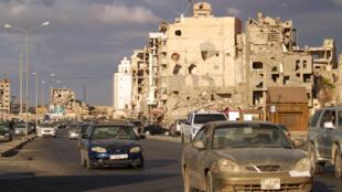 سيارات بالقرب من مبان نخرتها القذائف في مدينة بنغازي الساحلية شرق ليبيا في 23 تشرين الأول/أكتوبر 2020 بعد توقيع اتفاق لوقف إطلاق النار بين الفصائل المتحاربة في البلاد