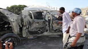 أشخاص ينظرون إلى سيارة في موقع الانفجار بالقرب من البرلمان الصومالي، مقديشو في 15 يونيو/حزيران 2019
