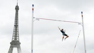 L'athlète français Renaud Lavillenie participant à une compétition de saut à la perche devant la tour Eiffel, à Paris, le 28 juin 2014.