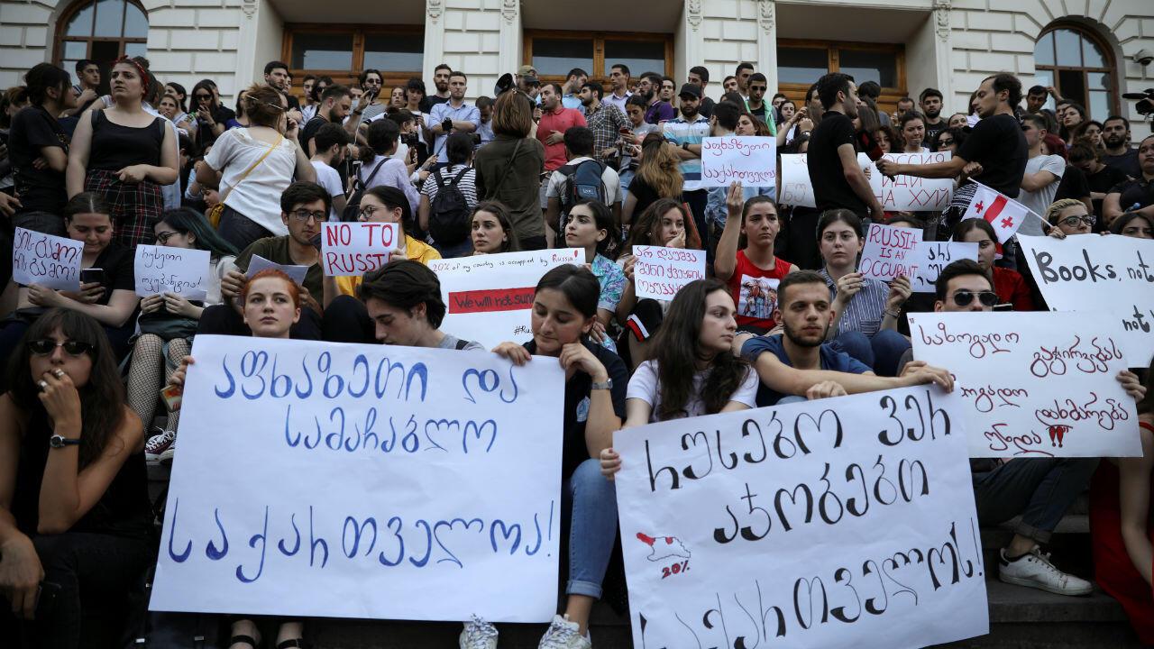 Manifestantes, incluidos estudiantes, asisten a un mitin contra la visita de un legislador ruso, en las afueras del Parlamento. 21 de junio.