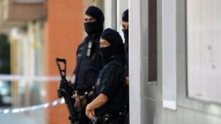 شرطيون كاتالونيون قرب مبنى عاش فيه مهاجم الشرطية في كورنيلا بالقرب من برشلونة 20 آب/أغسطس 2018.