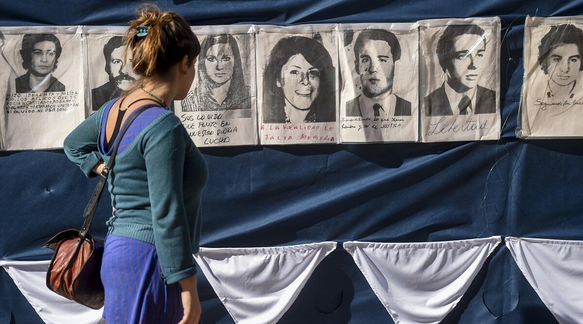 Dimanche 30 avril 2017, place de Mai à Buenos Aires, une passante regarde les portraits des disparus.