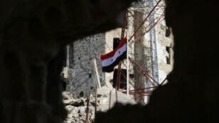 العلم السوري يرفرف وسط المباني المتضررة في درعا البلد في 12 تموز/يوليو 2018