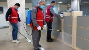 أعضاء في الهلال الأحمر الليبي يقومون بتعقيم أحد المكاتب الحكومية بمصراته (غرب)، 21 مارس/آذار 2020.