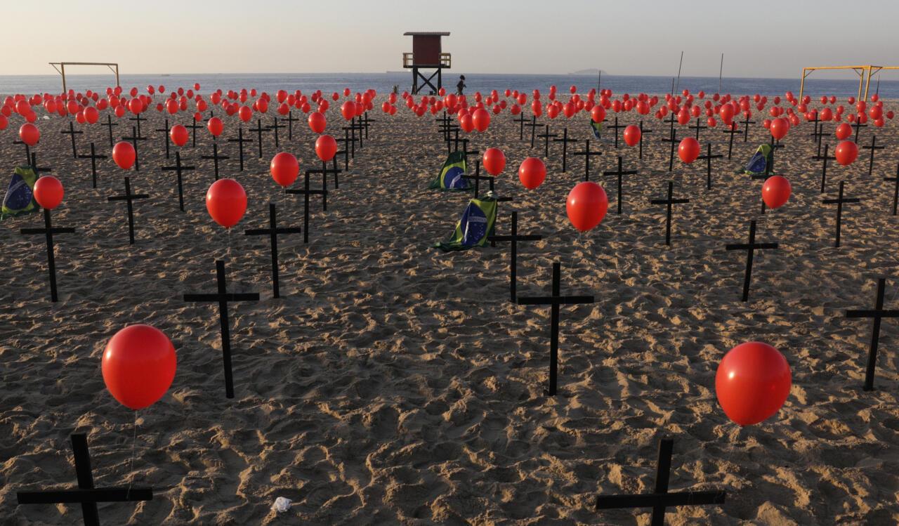 Una mujer pasa corriendo cruces y globos colocados por miembros de la ONG Río de Paz en homenaje a las cien mil víctimas mortales de Covid-19 en el país, en la playa de Copacabana en Río de Janeiro, Brasil el 8 de agosto de 2020.