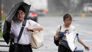 Dos peatones contra el fuerte viento generado por el paso del tifón Faxai en Tokio, Japón, el 9 de septiembre de 2019.